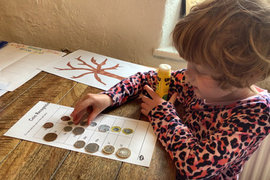 Lily busy completing one of the coin activities from this week's maths.