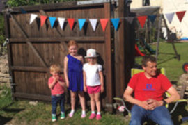 Isobel and her family all set for their back lane VE Day party. Look carefully to see the colours they are all wearing.