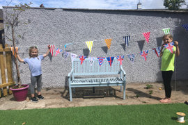 Izzy and her sister putting up bunting ready for the VE day celebrations.