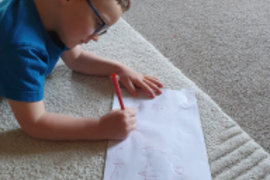 The look of concentration whilst completing his phonics work - well done Asher!