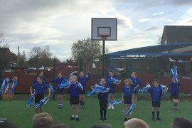 """Cheerleaders open our celebration performing to our school song """"We are the children of Catforth School""""."""