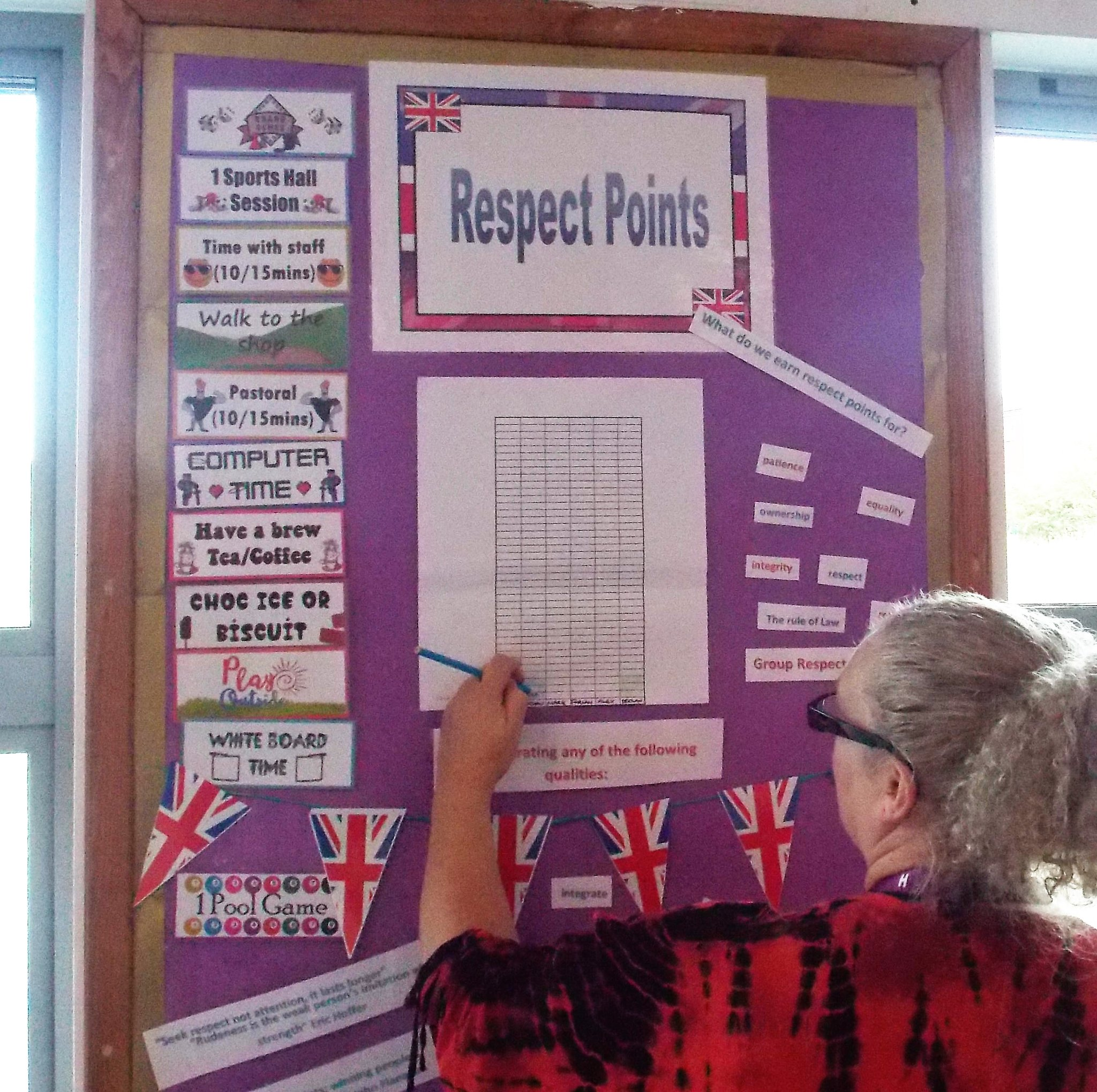 Image show staff member adding respect points to British Values board