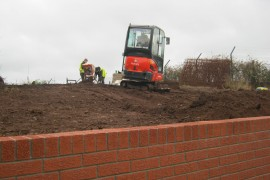 The Kubota digger levelling the soil.
