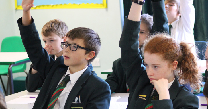 Pupils raise their hands in class.